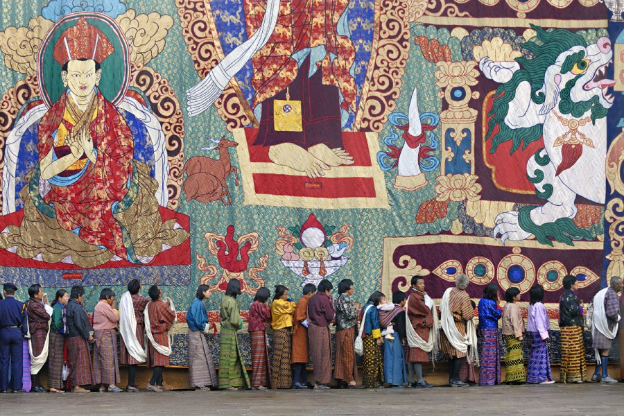 PILGRIMS QUEUEING FOR BLESSINGS AT THE BOTTOM OF A HUGE THANGKA OR THONGDREL, PUNAKHA TSECHU (FESTIVAL), PUNAKHA, BHUTAN