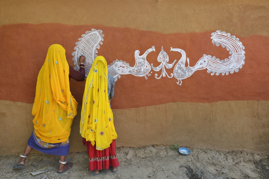 India, Rajasthan, Tonk region, Women painting clay walls prior to Diwali festival.
